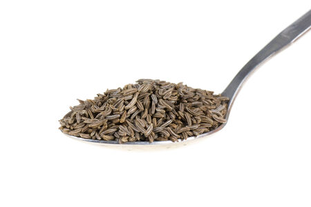 cumin: Cumin on a spoon isolated on white background Stock Photo