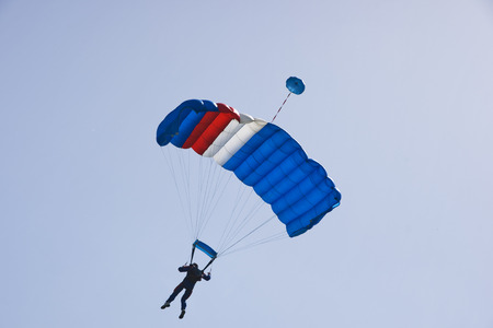 gliding: Parachutist jumping on a background of blue sky