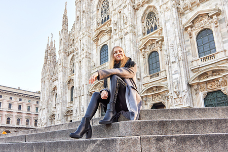 Happy girl sitting and smiling in front of Duomo of Milan Italy during the morning 免版税图像