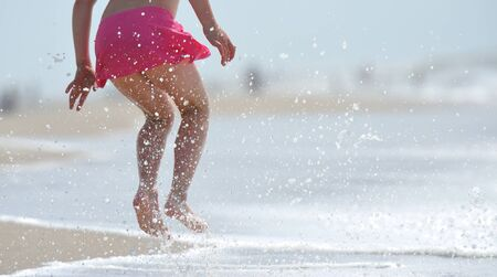 A young girl having fun on the beach jumping and running through the waves. Water splashing ...