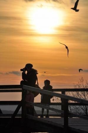 A photographer and a child in the sunset. Seagulls in the sky. Stock Photo