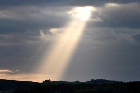 hoopt: Een zonnestraal breken door donkere wolken. Stockfoto