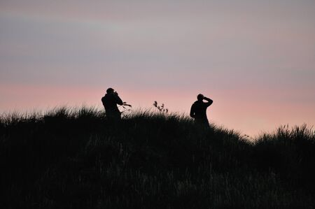 The silhouette of a photographer and his model in the sunset.