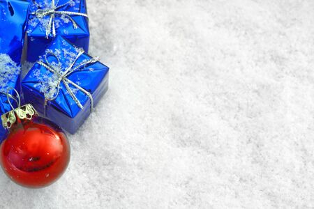 Blue Christmas gifts in the snow + red ball Stock Photo