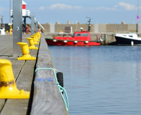 bollards: Docks with yellow bollards. A red boat in the background.