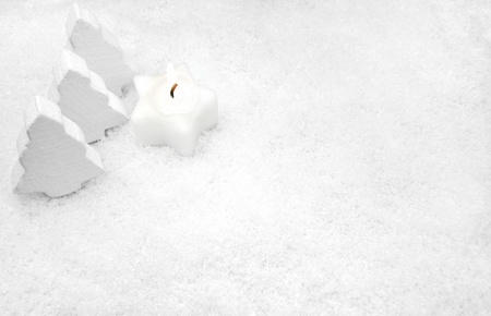 White candle and fir trees in the snow
