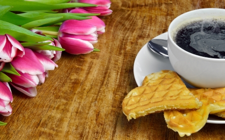 Fresh tulips, a cup of hot, steaming coffee and freshly baked waffles photo