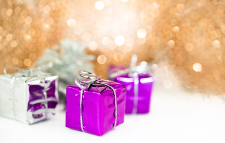 Christmas gifts in the snow in front of a glittering background