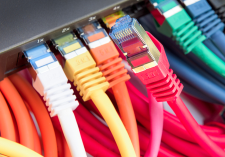 network cables: Colorful network cables connected to a switch Stock Photo
