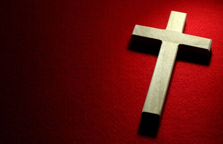 Closeup of wood crucifix on red felt background. Stock Photo