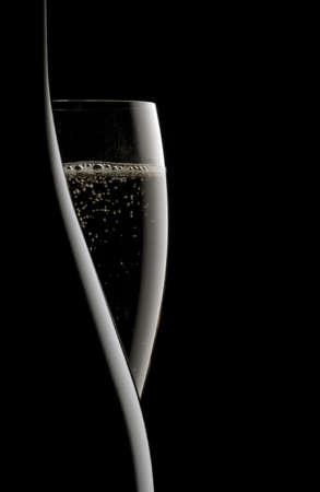 brindisi champagne: bottiglia di champagne e flauto su sfondo nero Archivio Fotografico