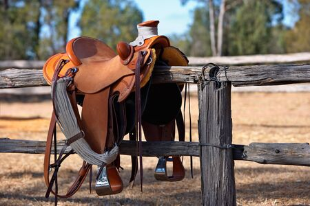 tacks: A western style saddle siting upon a country fence beside a riding arena. Stock Photo