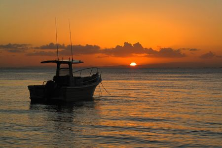 fishing scene: A boat at anchor on calm water with a colorful orange sunset in background.