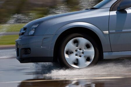 A modern vehicle being driven through water on a wet road Stock Photo