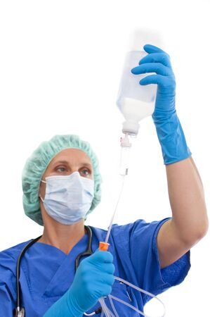 stethoskope: masked nurse preparing and controlling an infusion Stock Photo