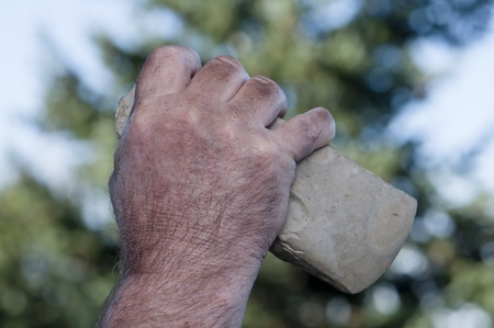 neanderthal  man: filthy hand of caveman holding handaxe