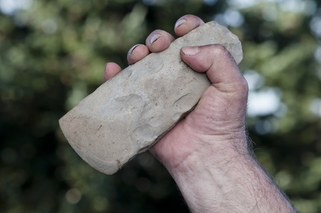 filthy hand of caveman holding handaxe photo