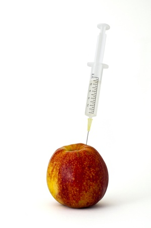 syringe stuck into an apple photo