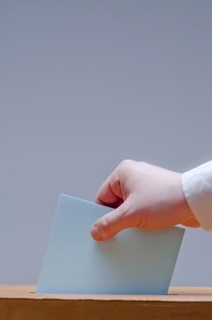 kiezer zet stembiljet in een stembus