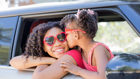 Summer fun! Happy girls or sisters with heart shaped sunglasses in car window. Younger girl kisses older girl on cheek in celebration of love, summer holiday, road trip or valentines day. Banque d'images