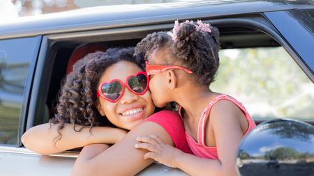 Zomerplezier! Gelukkige meisjes of zussen met hartvormige zonnebril in autoraam. Het jongere meisje kust ouder meisje op wang in viering van liefde, de zomervakantie, wegreis of de dag van Valentijnskaarten. Stockfoto - 78768922