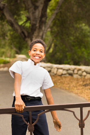 Happy African American boy standing, playing, or swinging on iron gate outside in front of trees at park. Space for copy in background area. Stock Photo