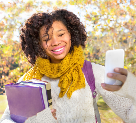 Attractive Black African American Student in Fall with Phone holding books while taking Selfie. Room for copy or text. Stock Photo
