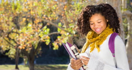 Pretty African American Black female student texting or using mobile phone. Room for copy or text over Fall trees in background .