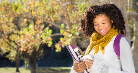 Schwarze Studentin des hübschen Afroamerikaners, die Handy simst oder verwendet. Raum für Kopie oder Text über Fallbäumen im Hintergrund.