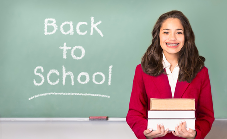 Back to School. Pretty ethnic or Hispanic teen with braces, wearing a red school uniform blazer isolated in front of green chalkboard with Back to school written on board in chalk. Banco de Imagens