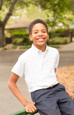 Happy Black African-American boy sitting on iron gate  in front of house in neighborhood. Space for copy in background area.