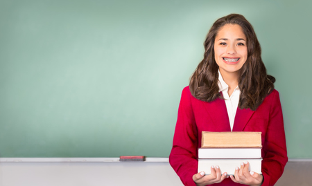Back to School. Pretty ethnic or Hispanic teen with braces, wearing a red school uniform blazer isolated in front of green chalkboard with Back to school written on board in chalk. Stock Photo