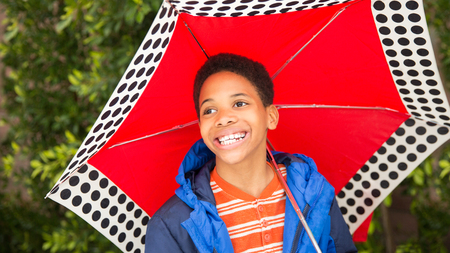 Cute happy African American or black boy holding red umbrella and wearing blue rain coat. Laughing, smiling, boy looks up at sky. Copy space on right for text or lettering. Background, selective focus