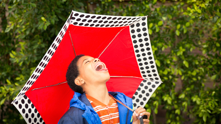 Cute happy African American or black boy wearing blue rain coat, tasting rain on his tongue while holding a colorful red umbrella with polka dots. Text Copy space. Background, selective focus