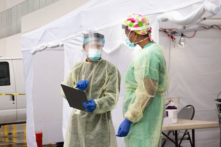 Healthcare providers test for CoVid19 and discuss antidote and testing in sterile make shift tent during global epidemic.