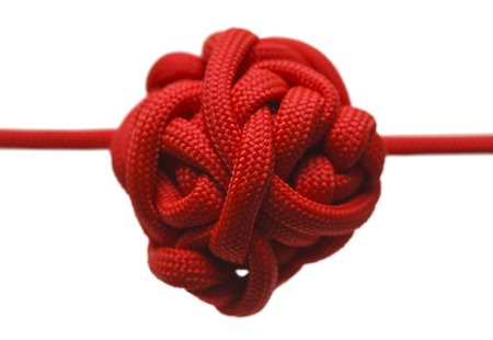 mess: Red Rope in a Large Knot Isolated on White Background. Stock Photo