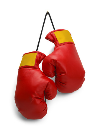 Pair of Red Boxing Gloves Hanging Isolated on White Background. Stock Photo