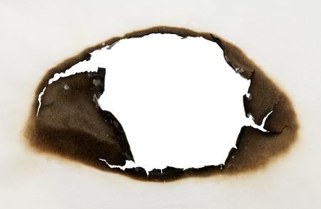 papel quemado: Pedazo de papel con el agujero quemado en forma oval con fondo blanco.