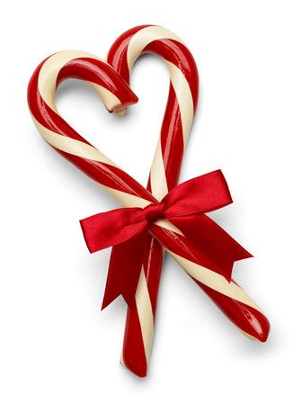 Twee snoep stokken in hartvorm met rode strik op een witte achtergrond.