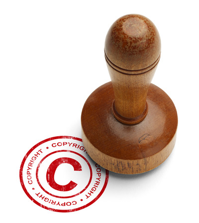 property rights: Red Copyright Stamp with Wooden Stamper Isolated on White Background.