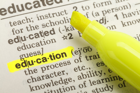 The Word Education Highlighted in Dictionary with Yellow Marker Highlighter Pen.