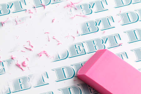 Pink eraser erasing multiple debts written in money font.
