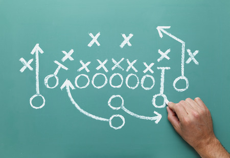 american football background: Football play drawn on Green Chalk Board with Hand. Stock Photo