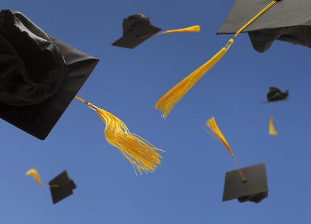 gorros de graduacion: Graduación Sombrero Negro Toss en el aire con borlas amarillas Foto de archivo