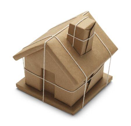 chimney corner: Casa envuelto en papel marr�n y cuerda aislado en el fondo blanco.