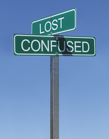 off course: Two Green Street Signs Lost and Confused on Metal Pole with Blue Sky Background.