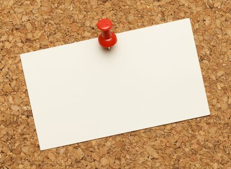 pin board: Business card posted on a cork board with red tack pin. Stock Photo