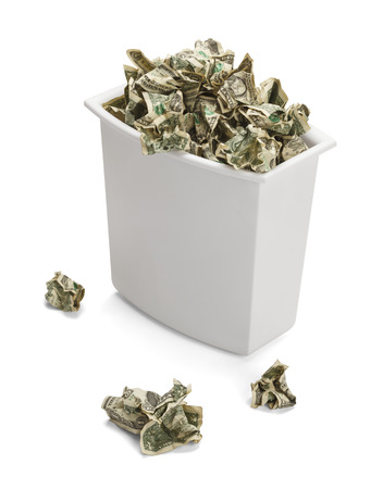 economic depression: Trash Can full of Crumpled Dollars Over Flowing of Frustration. Isolated on a white background.