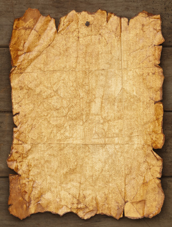 Worn and Ripped Paper Tacked on Wood Background with Copy Space. Archivio Fotografico