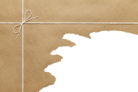 Brown Paper Package with Rope Torn Open on WHite Background. photo